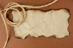 Burnt paper and flax string. On brown background Royalty Free Stock Photo
