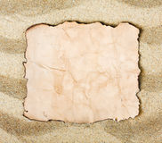 Burnt paper on the sea sand Royalty Free Stock Image
