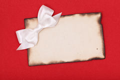 Burnt paper and white bow Royalty Free Stock Photos