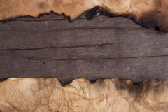 Burnt paper on wooden table. Royalty Free Stock Photos
