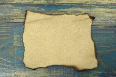 Burnt papier na błękitnym starym drewnianym tle Zdjęcia Stock