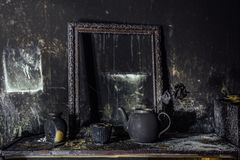 Burnt room interior. Burnt still life. Charred wall, picture frame, pot with burned rose in black soot.  royalty free stock image