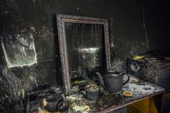Burnt room interior. Burnt still life. Charred wall, picture frame, pot with burned rose in black soot.  royalty free stock photography
