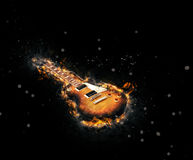 Burnt and scorched electric guitar. With residual flames still smouldering around the edge of deep scorch marks over a textured black background with copyspace Stock Photography