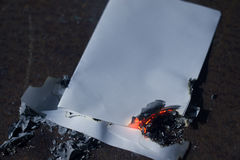 Burnt sheet of paper on dark. Charred sheet of white paper on a black background royalty free stock photos