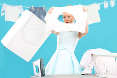 Burnt shirt - the perfect housewife . Young housewife overwhelmed by tasks associated with running a home. Joyful woman does housework. Colourful , humorous Royalty Free Stock Images