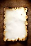 Burnt  textured paper on a wooden wall Royalty Free Stock Image