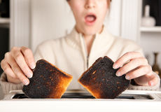 Burnt toast. Hands of a woman taking burnt toast out of a toaster Stock Images