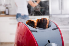 Burnt Toast Coming Out Of Toaster. Close-up Of Burnt Toast Coming Out Of Toaster In Kitchen royalty free stock photography