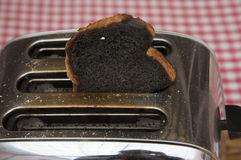 Burnt toast popping out of toaster Royalty Free Stock Image