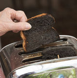 Burnt toast popping out of toaster Stock Photography