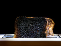 Burnt toasts. Two burnt toast slices sticking out of toaster over black background Royalty Free Stock Photography