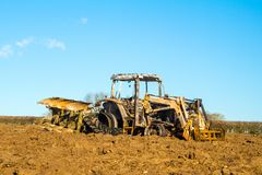 Burnt tractor digger in ploughed field Stock Photography