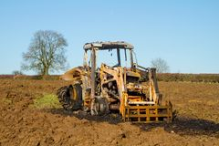 Burnt tractor digger in ploughed field Royalty Free Stock Photo