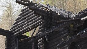 Burnt wooden log house, charred wood