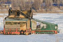Burnt wooden structure standing on ice of river Stock Photography