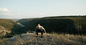 Burpee man doing burpees exercise fitness workout in amazing nature landscape. Fit male sport model training crossfit stock video footage