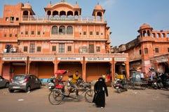 burqa礼服的回教妇女走通过自行车人力车和古城墙壁 库存照片