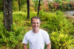 Burr Pond State Park Autumn New England caucasian man. A middle aged man smiling on a path with the fall colors of autumn in the background at Burr Pond State royalty free stock photos