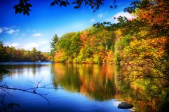 Burr Pond State Park Autumn New England. The green and changing colors trees reflecting off of the blue waters in Burr State Park in Torrington, Connecticut on a royalty free stock photos