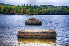 Burr Pond State Park Autumn New England. The green and changing colors trees reflecting off of the waters in Burr State Park in Torrington, Connecticut on a stock images