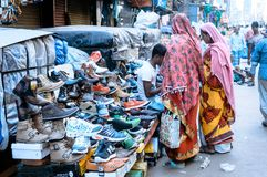 Burrabazar, Kolkata, India MAY, 2017: A seller is selling shoes in the street market. Burrabazar Bara Bazaar is a marketplace royalty free stock image