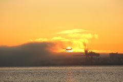 Burrard Inlet Floatplane at Sunrise, Vancouver. Floatplane takes off over Burrard Inlet through the rising sun. Vancouver, British Columbia, Canada Royalty Free Stock Photography