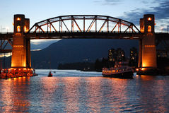 Burrard street bridge in vancouver. A dinner cruise ship moves into false creek under the lit up burrard street bridge in vancouver bc Royalty Free Stock Photography