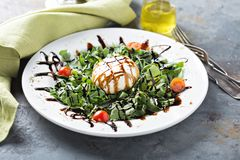 Burrata and arugula salad. With balsamic vinegar stock images