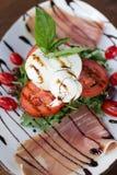 Burrata Caprese. Burrata Mozzarella Caprese accompanied by olives, prosciutto, and arugula Stock Photography
