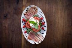 Burrata Caprese. Burrata Mozzarella Caprese accompanied by olives, prosciutto, and arugula Royalty Free Stock Images