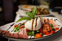 Burrata Caprese. Burrata Mozzarella Caprese accompanied by olives, prosciutto, and arugula Stock Images