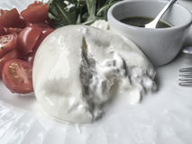 Burrata cheese that is filled with soft, stringy curd and cream. Stock Photos