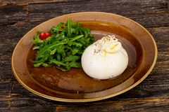 Burrata cheese with oil. And ruccola stock photo