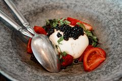 Burrata cheese with seaweed caviar and fruits, toned. Burrata cheese with seaweed caviar and fruits in stoneware plate, toned image royalty free stock photos