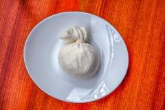 Burrata, fromage à pâte molle italien du sud typique a rempli du beurre, dans un plat avec le fond en bois images stock