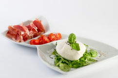 Burrata. With prosciutto on white plate stock photography