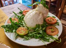 Burrata of Puglia seasoned and piled with wild rocket salad. Typical burrata of Puglia on a rustic presentation of a trattoria in Lecce; seasoned and piled with stock images