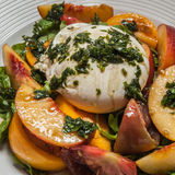 Burrata Salad. Delicious fresh burrata, peach and tomato salad royalty free stock photography