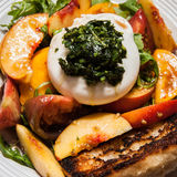 Burrata Salad. Delicious fresh burrata, peach and tomato salad Stock Photos