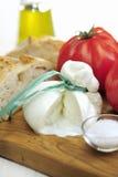 Burrata (sort of very fresh mozzarella cheese), tomato and bread Stock Photography