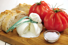 Burrata (sort of very fresh mozzarella cheese), tomato and bread Royalty Free Stock Photos
