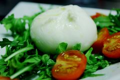 Burrata. Starter with burrata, rocket and tomatos. A typical Salento dish royalty free stock image
