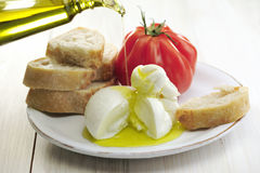 Burrata tomato and bread. Burrata (sort of very fresh mozzarella cheese), tomato and bread, olive oil being poured on cheese, selective focus stock photos