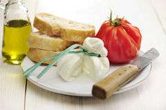 Burrata, tomato and bread. Burrata (sort of very fresh mozzarella cheese), tomato and bread, selective focus royalty free stock photography