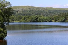 Burrator Lake and view of tor. Burrator reservoir lake located in Dartmoor National Park,Devon UK with trees and tor in the distance on a bright sunny day royalty free stock photos