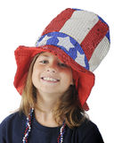 Burried Under Uncle Sam's Hat. Close-up of a pretty elementary girl looking up from under a sparkly, oversized Uncle Sam hat. On a white background stock images