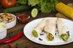 Burrito auf Platte auf hölzernem Hintergrund stockfoto