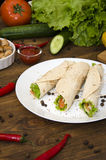 Burrito auf Platte mit Gemüse und Pfeffer Stockfotos