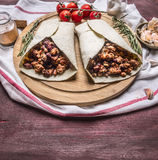 Burrito com carne e vegetais em uma placa de corte com tomates e fim rústico de madeira do fundo do alho acima Fotos de Stock Royalty Free